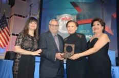 Nydia M. Velásquez, congresista de New York recibe el Premio Liderazgo por solución a la crisis de Puerto Rico, de manos de  el doctor Edwin Meléndez, del Comité Ejecutivo de NCLR (centro). Con ellos, la presidenta de la Junta Directiva (izq.) y Janet Murguía, presidenta y directora de NCLR. Ceremonia el 8 de marzo en el National Building Museum.