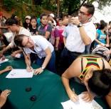 Una mujer sonríe mientras firma una petición para iniciar un referendo revocatorio del mandato del presidente de Venezuela, Nicolás Maduro, en San Cristóbal, Caracas, el miércoles 27 de abril. Foto: Fernando Llano / AP