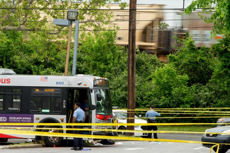 La policía trabaja en la escena del crimen, lego de que las autoridades dijeron que un hombre atacó a un conductor de autobús, robó el vehículo y luego atropellara y matara a un hombre, después de que el bus se subió a una acera en una estación de combustible.   Fotos: AP