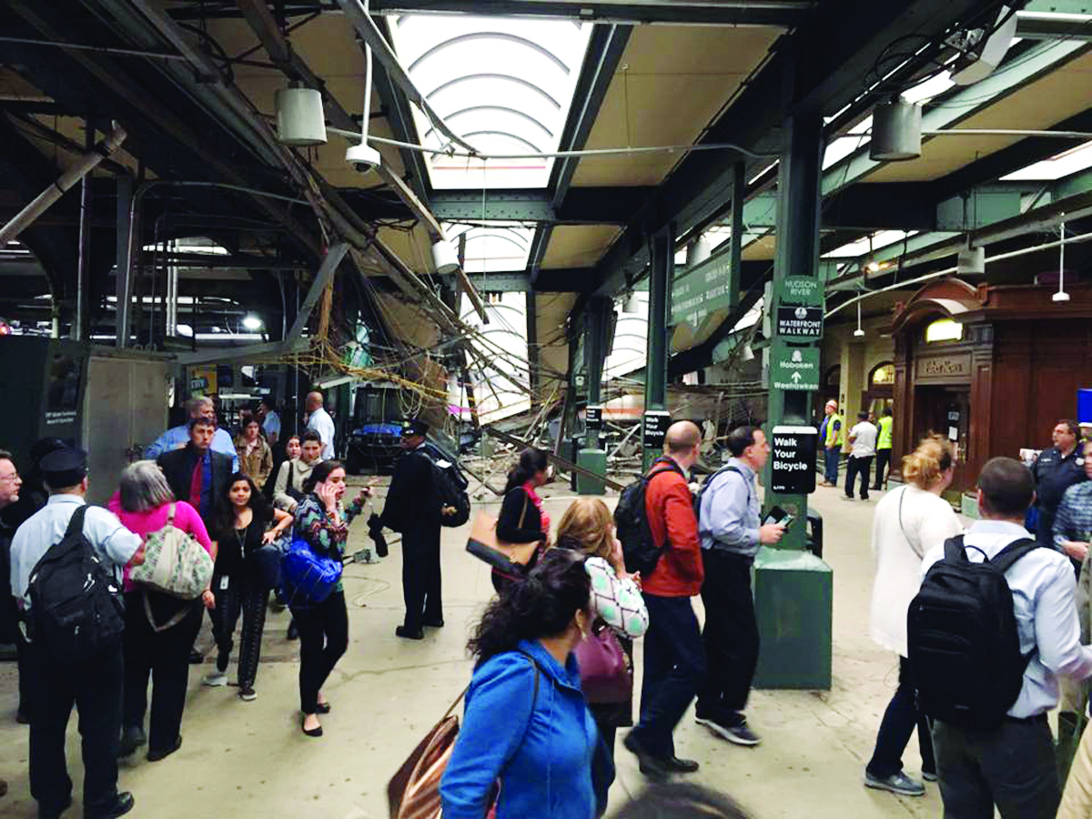 This photo provided by Brian Farnham shows the inside of the Hoboken station after a commuter train crash on Thursday, Sept. 29, 2016 in Hoboken, N.J.   A commuter train plowed into the bustling rail station during the morning rush hour Thursday, injuring more than 100 people in a tangle of broken concrete, twisted metal and dangling cables, authorities said. (Brian Farnham via AP)