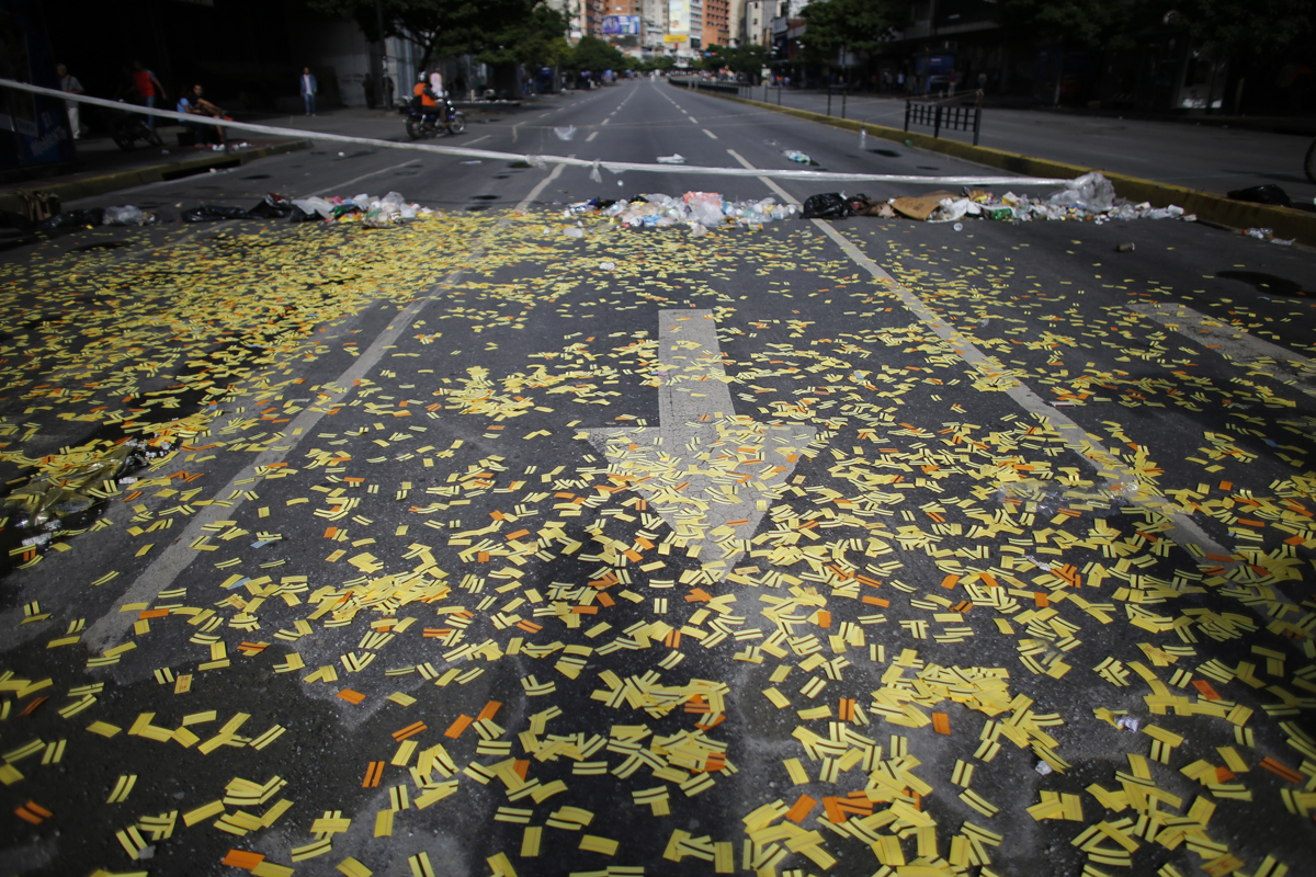 A street is blanketed with metro tickets near a roadblock set up by anti-government protesters in Caracas, Venezuela, Thursday, July 20, 2017. Venezuelan President Nicolas Maduro and his opponents face a crucial showdown Thursday as the country's opposition calls a 24-hour national strike. The country's largest business group, Fedecamaras, has cautiously avoided full endorsement of the strike, but its members have told employees that they won't be punished for coming to work. (AP Photo/Ariana Cubillos)