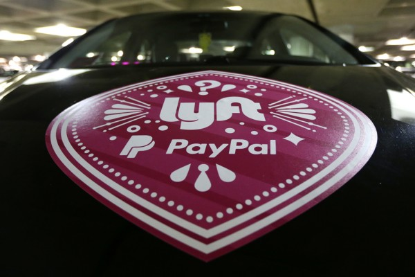 FILE - In this March 31, 2016, a Lyft ride-hailing service logo is displayed on a vehicle at Seattle-Tacoma International Airport in Seattle. Lyft is setting up its own unit to develop autonomous vehicle technology, but its approach will be different from other companies and partnerships working on self-driving cars. The San Francisco-based ride-hailing service says it will open its network, inviting automakers and tech companies to use it to haul passengers and gather data. . (AP Photo/Ted S. Warren, File)
