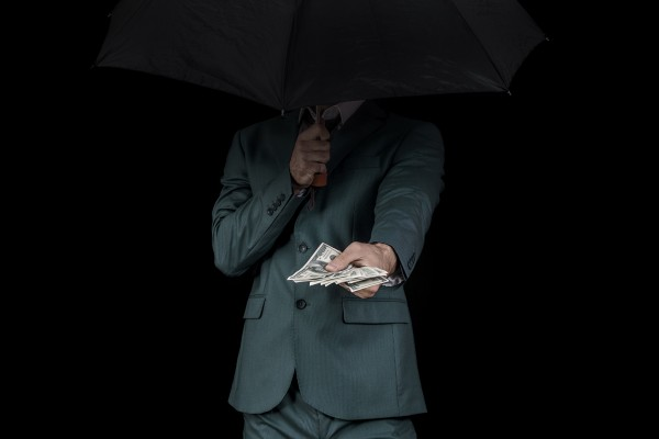 Man hiding behind an umbrella, offering money