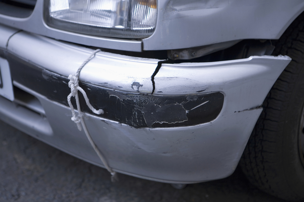 Motor vehicle showing damage to bumper trim below headlight on front of car near number plate, secured to chassis with string