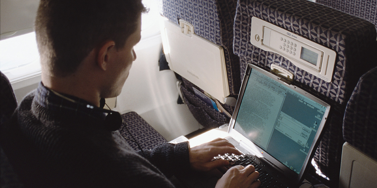 a caucasian man works on his laptop computer on an airplane