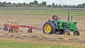 Arnie Zent turns a windrow of field grass south of Bismarck, N.D., Thursday, Aug. 10, 2017, with plans to have it baled before the weekend.