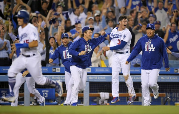 Members of the Los Angeles Dodgers, right, celebrate as Austin Barnes, left, scores the winning run on a double by Yasiel Puig during the ninth inning of a baseball game against the Chicago White Sox, Wednesday, Aug. 16, 2017, in Los Angeles. The Dodgers won 5-4. (AP Photo/Mark J. Terrill)