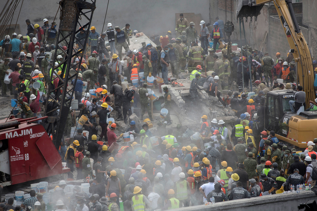 Emergency personnel search for survivors in a collapsed building in Mexico City, Mexico, Wednesday, Sept. 20, 2017. A 7.1 magnitude earthquake struck southern Mexico dealing a devastating amount of damage to buildings in Mexico City. (AP Photo/Anthony Vazquez)