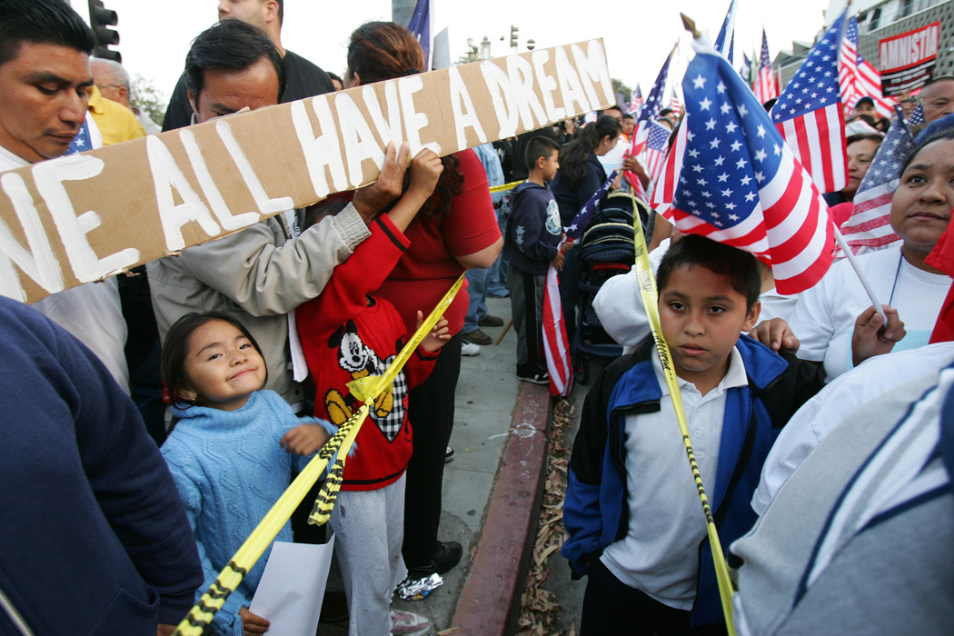 """Jarira Perez (L) stands with her father Alfonso Perez from Mexico who holds a sign reading """"We All Have A Dream"""" as immigration rights marchers arrive at MacArthur Park near downtown Los Angeles, California, 17 May 2007.  The procession and rally was called to protest police actions during a 01 May immigrants' rights march in MacArthur Park.  AFP PHOTO/ROBYN BECK"""