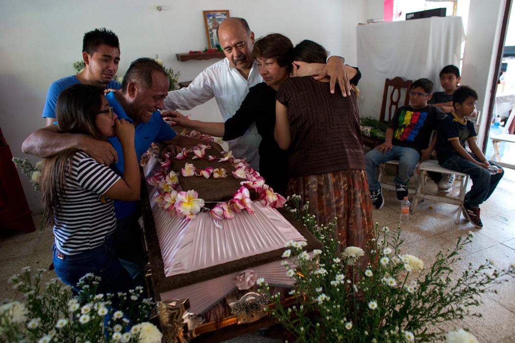 Los miembros de una familia lloran sobre el ataœd con los restos de Reynalda Matus, de 64 a–os, en Juchit‡n, en el estado sure–o de Oaxaca, en MŽxico, el s‡bado 9 de septiembre de 2017. Matus muri— cuando la farmacia donde trabajaba colaps— durante el sismo de 8,1 que sacudi— MŽxico el jueves 7 de septiembre de 2017. (AP Foto/Rebecca Blackwell)