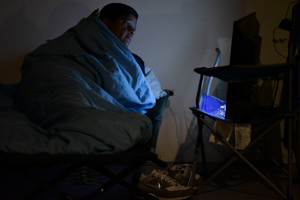 A woman watches television while waiting at Humacao Arena refugee center for the imminent impact of Maria, a Category 5 hurricane that threatens to hit the eastern region of the island with sustained winds of 175 miles per hour, in Humacao, Puerto Rico, Tuesday, September 19, 2017. About 137 citizens arrived at the refuge from different parts of the eastern region of the Island. (AP Photo/Carlos Giusti)