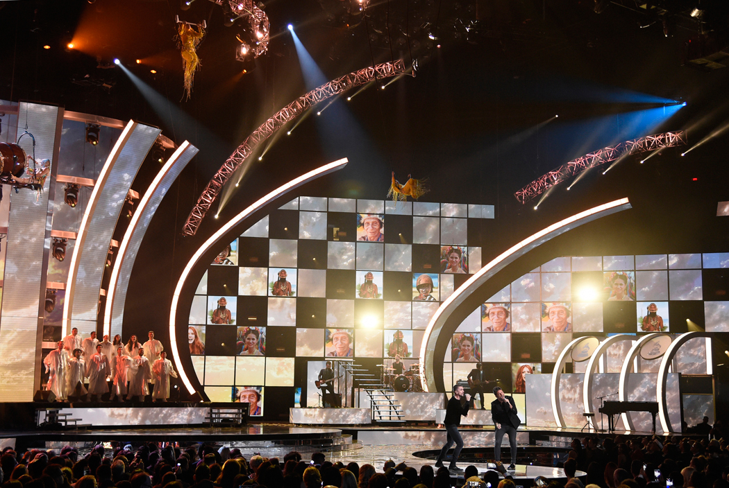 """FILE - In this Nov. 17, 2016 file photo, Juanes, center left, and Pablo Lopez perform """"Tu Enemigo"""" with the cast members from Cirque du Soleil """"Mystere"""" at the 17th annual Latin Grammy Awards at the T-Mobile Arena in Las Vegas. On Tuesday, Sept. 19, 2017, the Latin Recording Academy announced that because of the earthquake in Mexico and hurricanes that have ravaged Hispanic communities in the U.S. and the Caribbean, it is postponing the announcement of nomineees for this year's 18th annual Latin Grammy awards. (Photo by Chris Pizzello/Invision/AP, File)"""