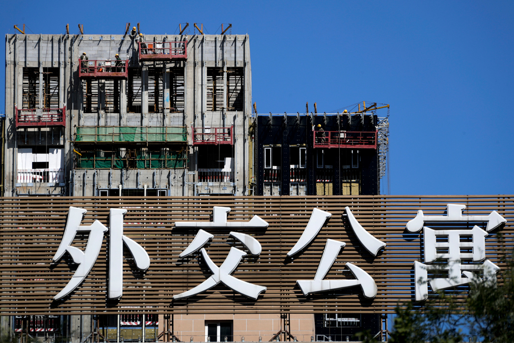Workers on a suspended platform weld steel frames on a new apartment construction site at the Diplomatic Residence Compound in Beijing, Sunday, Sept. 17, 2017. China's government says Chinese investment in other countries has plunged since Beijing tightened controls to discourage purchases of sports teams and other assets deemed unneeded for national development. (AP Photo/Andy Wong)