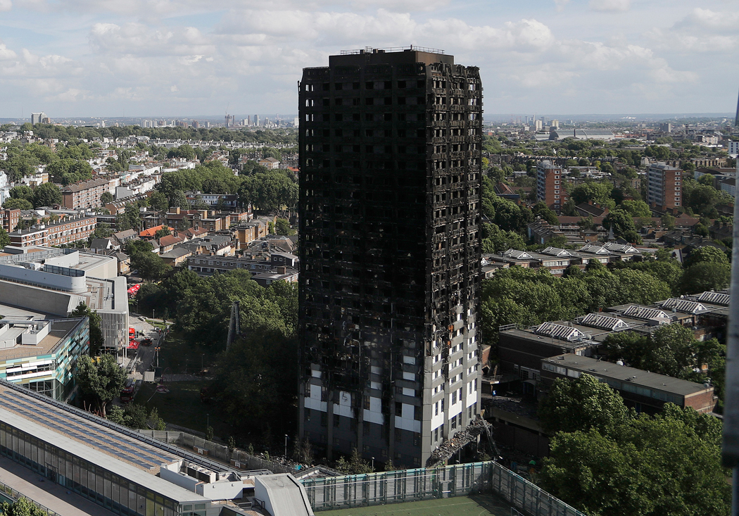 FILE - This is a Thursday, June 15, 2017 file photo of The scorched facade of the Grenfell Tower in London after a massive fire raced through the 24-storey high-rise apartment building in west London. British police said Tuesday, Sept. 19, 2017, the number of people who died in the Grenfell Tower fire in west London may be slightly lower than the 80 previously estimated.  (AP Photo/Frank Augstein/File)