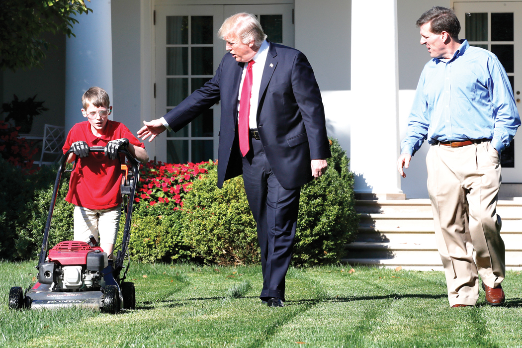 Frank Giaccio, 11, of Falls Church, Va., left, is accompanied by President Donald Trump as he mows the lawn of the Rose Garden, Friday, Sept. 15, 2017, at the White House in Washington, with his father Greg Giaccio. The 11-year-old, who wrote the president requesting to mow the lawn at the White House, was so focused on the job at hand that he didn't notice the president until he was right next to him. (AP Photo/Jacquelyn Martin)