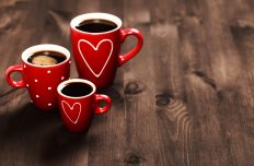 Three red coffee cups, with hearts and polka dots, standing on black wooden surface with place for text. Coffee for St. Valentine's Day.