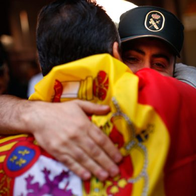 A demonstrator wearing a Spanish flag hugs a national police officer during a gathering in Barcelona, Spain, Sunday Oct. 8, 2017. Demonstrators gathered early in Barcelona on Sunday ahead of a march to show support for the Spanish union and call on Catalonia not to declare independence. (AP Photo/Francisco Seco)