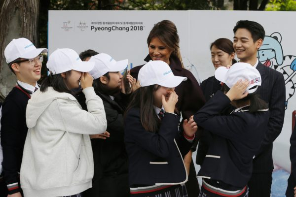 U.S. first lady Melania Trump is greeted by South Korean middle school students as Choi Min-ho, a member of South Korean boy band Shinee, top right, watches during
