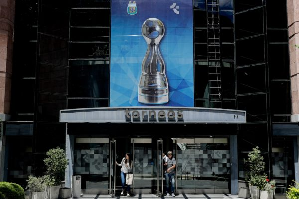 People walk out of the sports marketing company Torneos y Competencias office in Buenos Aires, Argentina, Thursday, Nov. 16, 2017. The former CEO of Torneos y Competencias Alejandro Burzaco, testified on Tuesday that the former President of the Argentine Football Association, AFA, Julio Grondona, demanded bribes to help cover what he was owed for his 2010 vote that helped Qatar land the tournament. (AP Photo/Natacha Pisarenko)