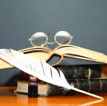 Literature concept. Still life with old spectacles on books near quill pen on wooden table