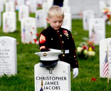 Christian Jacobs, 5, of Hertford, N.C., dressed as a Marine, pauses at his father's gravestone on Memorial Day at Arlington National Cemetery in Arlington, Va., Monday, May 30, 2016. Christian's father Marine Sgt. Christopher James Jacobs died in a training accident in 2011. (AP Photo/Carolyn Kaster)