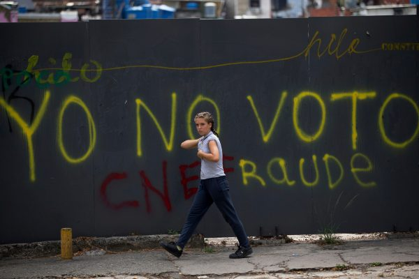 In this Friday, April 20, 2018 photo, a pedestrian walks past a graffiti written on a wall that reads in Spanish