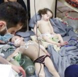 This image made from video released by the Syrian Civil Defense White Helmets, which has been authenticated based on its contents and other AP reporting, shows medical workers treating toddlers following an alleged poison gas attack in the opposition-held town of Douma, in eastern Ghouta, near Damascus, Syria, Sunday, April. 8, 2018. The Civil Defense said patients were having difficulty breathing and burning in their eyes. Syrian opposition activists and rescuers said Sunday that a poison gas attack on a rebel-held town near the capital. The Syrian government denied the allegations, which could not be independently verified. (Syrian Civil Defense White Helmets via AP)