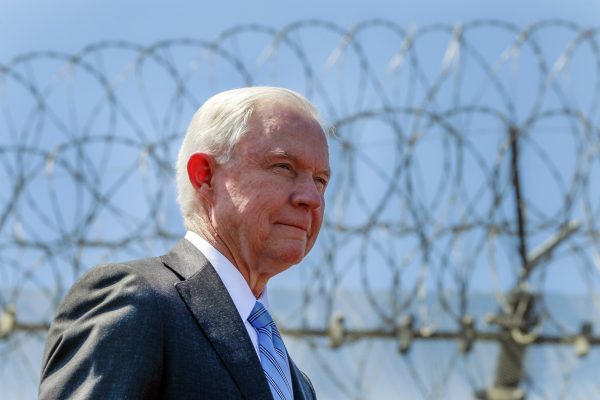 FILE - In this April 21, 2017 file photo, with razor wire across the top of the secondary border fence behind him, U.S. Attorney General Jeff Sessions attends a news conference at the U.S.-Mexico border next to the Brown Field Border Patrol Station in San Diego.  Immigration judges generally cannot consider domestic and gang violence as grounds for asylum, U.S. Attorney General Jeff Sessions said Monday, June 11, 2018 in a ruling that could affect large numbers of Central Americans who have increasingly turned to the United States for protection. (Hayne Palmour IV/The San Diego Union-Tribune via AP, File)