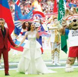 Robbie Williams, left, and Aida Garifullina, center, perform ahead of the group A match between Russia and Saudi Arabia which opens the 2018 soccer World Cup at the Luzhniki stadium in Moscow, Russia, Thursday, June 14, 2018. (AP Photo/Matthias Schrader)