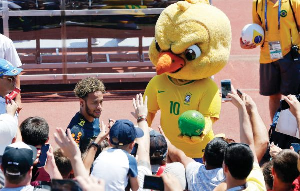 FILE - In this Tuesday, June 12, 2018 file photo Brazil's mascot holds a soccer ball as fans cheer Brazil's Neymar as he leaves a training session in Sochi, Russia. It took an angry-looking bird to get Brazilians hooked on their World Cup mascot. Brazil historically never fully embraced the tradition of mascots in sports, but things changed when the soccer federation _ inspired in part by Chicago Bull's