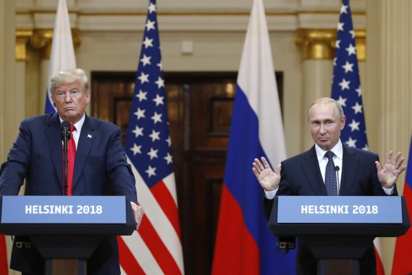 Russian President Vladimir Putin raises his hands as U.S. President Donald Trump, left, listens during a press conference after their meeting at the Presidential Palace in Helsinki, Finland, Monday, July 16, 2018. (AP Photo/Alexander Zemlianichenko)