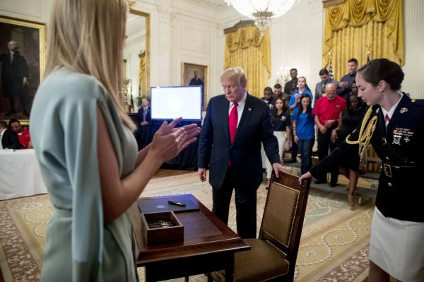 President Donald Trump, accompanied by Ivanka Trump, the daughter of President Donald Trump, left, sits down to sign an Executive Order that establishes a National Council for the American Worker during a ceremony in the East Room of the White House, Thursday, July 19, 2018, in Washington. (AP Photo/Andrew Harnik)