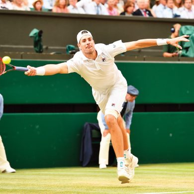 John Isner of the US returns a ball to Kevin Anderson of South Africa during their men's singles semifinal match at the Wimbledon Tennis Championships, in London, Friday July 13, 2018. (AP Photo/Glyn Kirk, Pool)