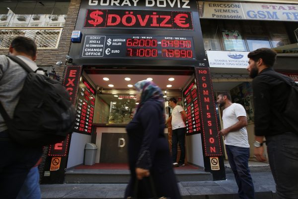 CORRECTING CAPTION BYLINE TO LEFTERIS PITARAKIS - People walk past a currency exchange shop in Istanbul, Tuesday, Aug. 14, 2018.The Turkish lira has nosedived in value in the past week over concerns about Turkey's President Recep Tayyip Erdogan's economic policies and after the United States slapped sanctions on Turkey angered by the continued detention of an American pastor. (AP Photo/Lefteris Pitarakis)