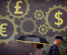 FILE - In this July 20, 2018 photo, people walk past a mural displaying world currency symbols on the outside of a bank in Beijing. Amid a worsening tariff battle, China is putting off accepting license applications from American companies in financial services and other industries until Washington makes progress toward a settlement, an official of a business group said Tuesday, Sept. 11, 2018. (AP Photo/Mark Schiefelbein, File)