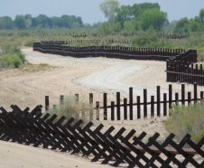 This June 15, 2017, photo provided by Kenneth Madsen, shows a post-on-rail style of fence along the flood plain of the Colorado River between Arizona and Baja California, which is typical of border wall fences placed in environmentally sensitive areas or in areas prone to flooding. A new photo exhibit by Madsen opening Wednesday, Sept. 19, 2018, at the Ohio State University-Newark campus,