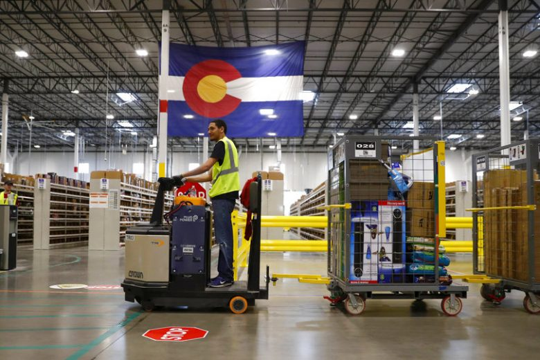 FILE- In this May 3, 2018, file photo an associate uses his vehicle to pull tugs loaded with goods during a tour of the Amazon fulfillment center in Aurora, Colo. Amazon is boosting its minimum wage for all U.S. workers to $15 per hour starting next month. The company said Tuesday, Oct. 2, 2018, that the wage hike will benefit more than 350,000 workers, which includes full-time, part-time, temporary and seasonal positions. (AP Photo/David Zalubowski, File)