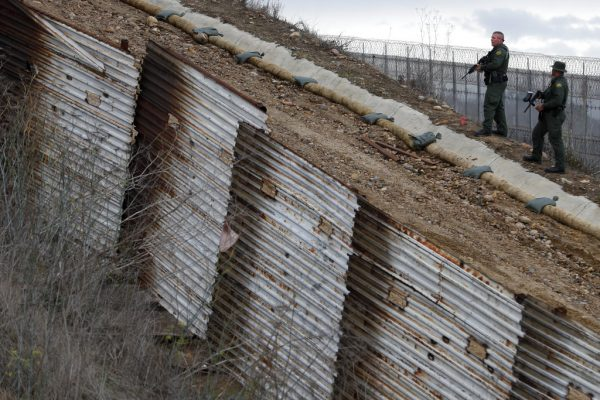 U.S. border patrol agents standing in San Ysidro, California stand watch as they respond to at least two men who got close to the U.S. border wall from the Mexican side, one with his face covered and another holding rocks, seen from Tijuana, Mexico, Thursday, Dec. 6, 2018. The incident diffused soon after and the agents left. (AP Photo/Rebecca Blackwell)