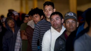 Honduran migrants stand in line for breakfast inside an empty warehouse that opened its doors to migrants in downtown Tijuana, Mexico, Tuesday, Dec. 18, 2018. The owner opened the warehouse for two months, after it had been empty for years, so some migrants don't sleep on the sidewalks. (AP Photo/Moises Castillo)