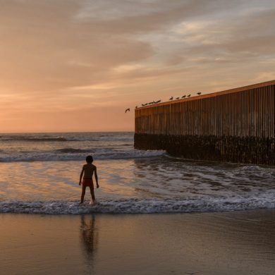 A boy stands at the sea by the U.S. border fence separating San Diego from Tijuana, Mexico, Sunday, Dec. 23, 2018. Discouraged by the long wait to apply for asylum through official ports of entry, many Central American migrants from recent caravans are choosing to cross the U.S. border wall and hand themselves in to border patrol agents. (AP Photo/Daniel Ochoa de Olza)