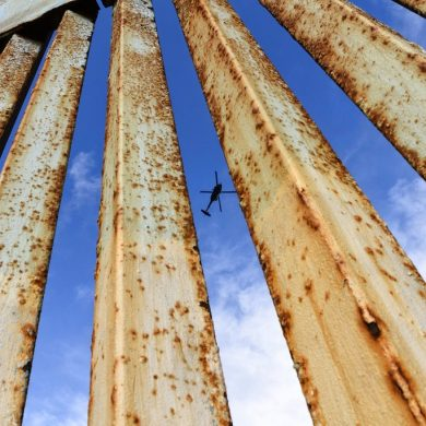 A helicopter monitors the U.S. border fence from above, seen from Tijuana, Mexico, Sunday, Dec. 23, 2018. A partial federal shutdown has been put in motion because of gridlock in Congress over funding for President Donald Trump's Mexican border wall. (AP Photo/Daniel Ochoa de Olza)