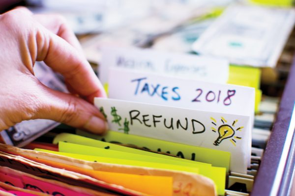 Hand pulling out file in filing cabinet with tax forms and papers with words Refund and Taxes 2018 handwritten on file folder conceptual dollar signs images and light bulb for ideas on tax refund conceptual financial planning photography