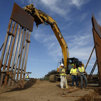 """FILE - In this Jan. 9, 2019 file photo, construction crews install new border wall sections seen from Tijuana, Mexico. Sen. Dick Durbin, D-Ill., says the Pentagon is planning to tap $1 billion in leftover funds from military pay and pensions accounts to help President Donald Trump pay for his long-sought border wall. Durbin told The Associated Press, """"it's coming out of military pay and pensions, $1 billion, that's the plan.""""(AP Photo/Gregory Bull, File)"""