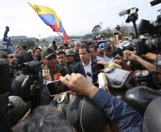 Venezuela's opposition leader and self-proclaimed president Juan Guaido, center, stands with an unidentified military officer who is helping to lead a military uprising, center left, as they talk to the press and supporters outside La Carlota air base in Caracas, Venezuela, Tuesday, April 30, 2019. Guaidó took to the streets with activist Leopoldo Lopez and a small contingent of heavily armed troops early Tuesday in a bold and risky call for the military to rise up and oust Maduro. (AP Photo/Fernando Llano)