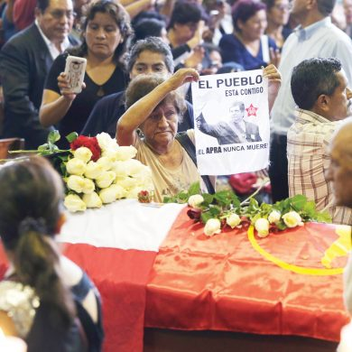 A supporter shows and an image of Peru's late President Alan Garcia on the second day of his wake at his party's headquarters in Lima, Peru, Thursday, April 18, 2019. Garcia shot himself in the head and died Wednesday as officers waited to arrest him in a massive graft probe that has put the country's most prominent politicians behind bars and provoked a reckoning over corruption. (AP Photo/Martin Mejia)