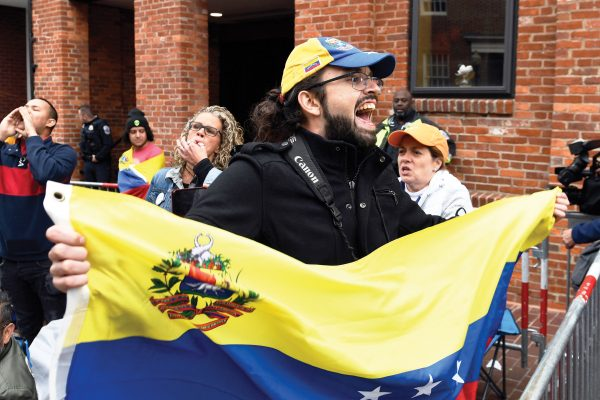Protester Andres Miguel Harris, who was born in Venezuela, protests with others outside the Venezuelan embassy in Washington, Tuesday, May 14, 2019. (AP Photo/Susan Walsh)