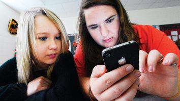 FILE - In this March 13, 2014, file photo, Hartselle High School students Lissa Blagburn and Brantlee Wright use an iPhone as they work on a networked lesson in Spanish class in Hartselle, Ala. Teachers say they're seeing so much student anxiety that a national union newsletter labels it a