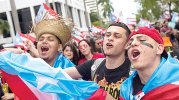 A trio of men sing during a march to celebrate the resignation of Gov. Ricardo Rossello who announced overnight that he is resigning Aug. 2 after weeks of protests over leaked obscene, misogynistic online chats, in San Juan, Puerto Rico, Thursday, July 25, 2019.(AP Photo/Dennis M. Rivera Pichardo)