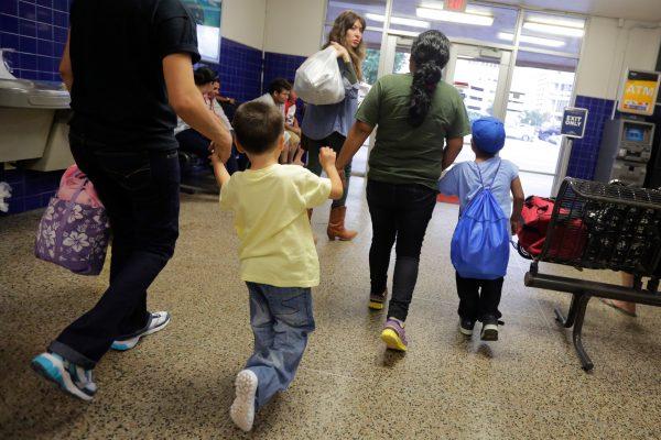 ARCHIVO - En esta imagen de archivo del 7 de julio de 2015, migrantes de El Salvador que entraron en el país sin permiso de residencia caminan hacia un autobús tras recibir autorización para salir de un centro de detención familiar en San Antonio, Texas. (AP Foto/Eric Gay, Archivo)