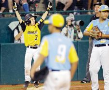 South Riding, Virginia's Noah Culpepper (2) stands on third base and celebrates his teammates Kian Henson double against Wailuku, Hawaii during the third inning of a baseball game at the Little League World Series tournament in South Williamsport, Pa., Wednesday, Aug. 21, 2019. (AP Photo/Tom E. Puskar)